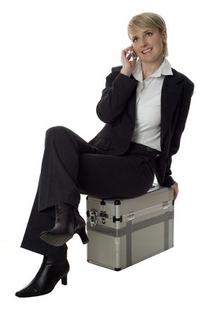 young business women sitting on case and talking on mobile photo