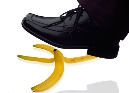 men shoe stepping on banana peel concept on white