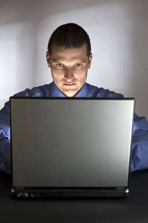 young business men working on laptop lit by light from it photo