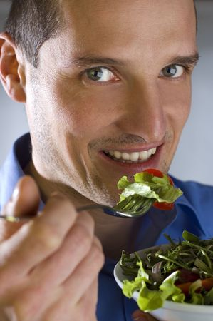 eat the plant: young men eating salad close up shoot