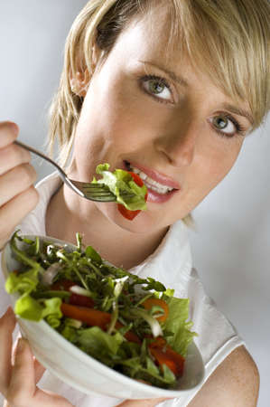young attractive woman eating salad close up Stock Photo