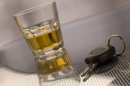 drink and drive: car keys with glass of whiskey in background - drink drive concept