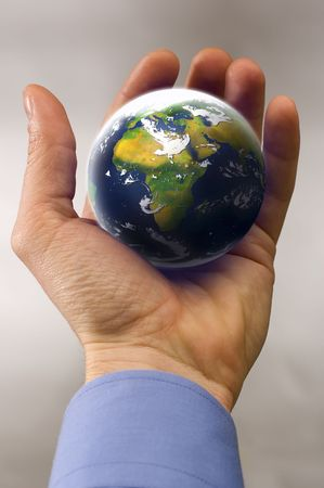 population growth: business man hand holding planet earth close up