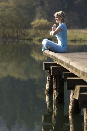 young girl relaxing on pier in early morning Stock Photo - 870225