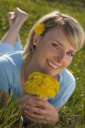 young blond girl holding flowers outside on grass photo