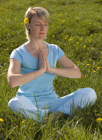 center position: blond young woman meditating outside on grass Stock Photo