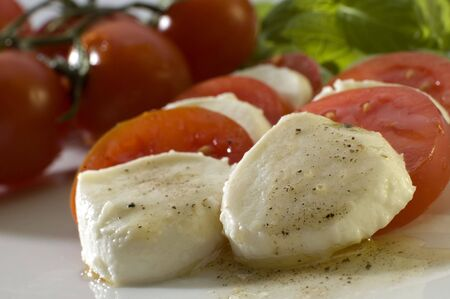 mozzarella with basil, tomatos and olive oil close up photo