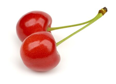 crimson colour: two red fresh cherry close up on white
