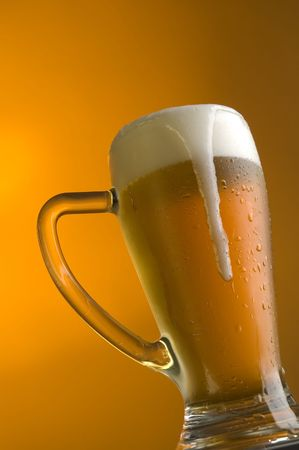 glass of beer on orange background close up Stock Photo - 1005776