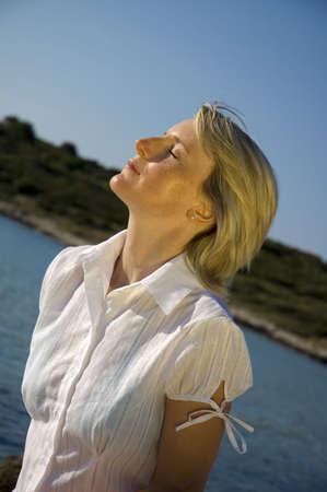 sun bathing: young blonde girl sun bathing beside the sea