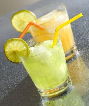 bartend: cold orange and lemon drinks close up