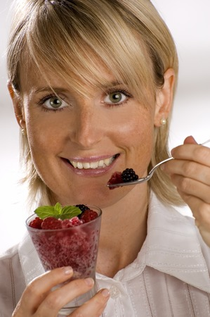 girl eating redcurrant or strawberry granita close up photo