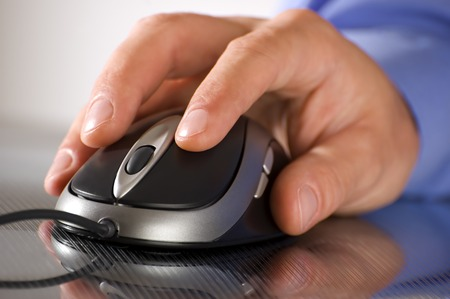loging: male business man hand on a computer mouse close up Stock Photo