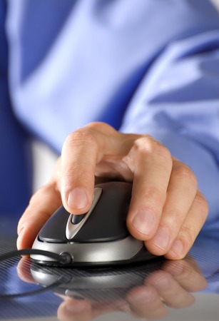 paypal: male business man hand on a computer mouse close up Stock Photo