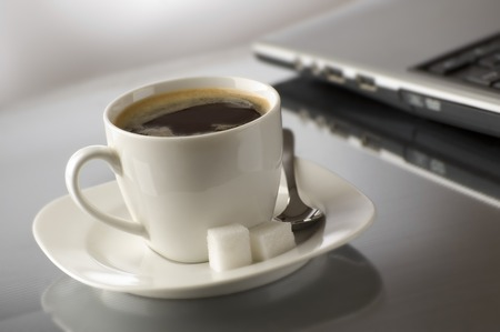 cup of hot coffee beside a laptop close up Stock Photo - 1525463