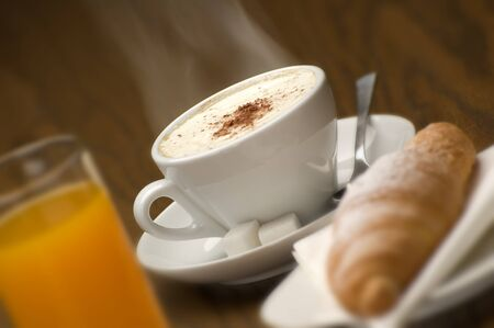 cup of cappuccino with croissant close up photo