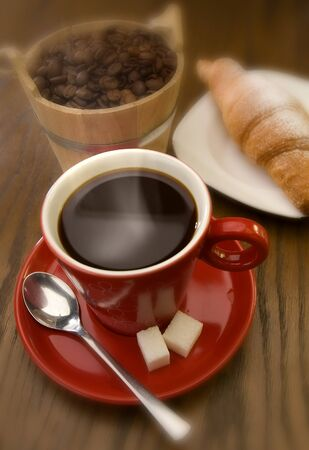 cup of black coffee with croissant close up photo