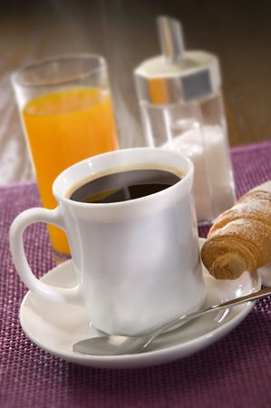 black coffee with croissant and juice close up photo