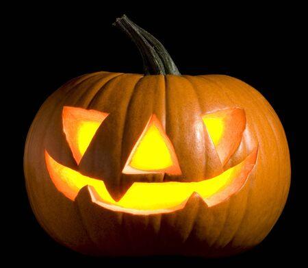 menacing: jack-o-lantern pumpkin on black background close up