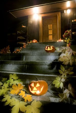 halloween pumpkins on stairs in front of the house at night photo