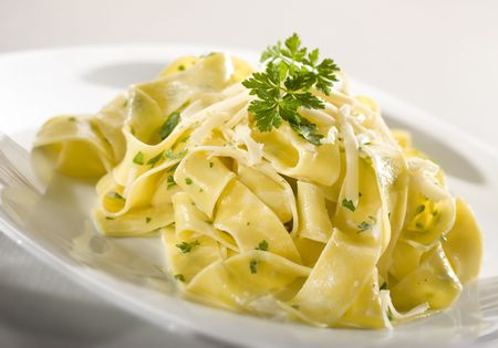 tasty pasta with cream, cheese and parsley close up