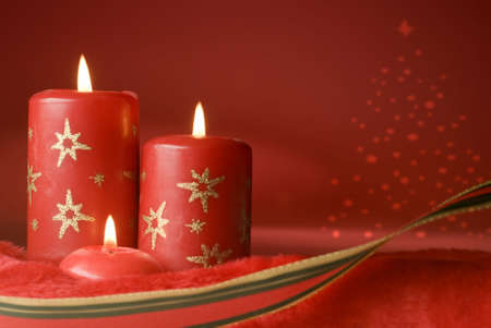 three red christmas candles on red background photo