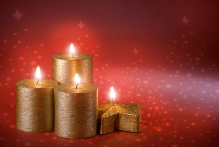 four golden christmas candles on red background photo