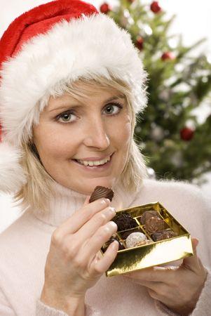 santa girl eating chocolate candy close up shoot photo
