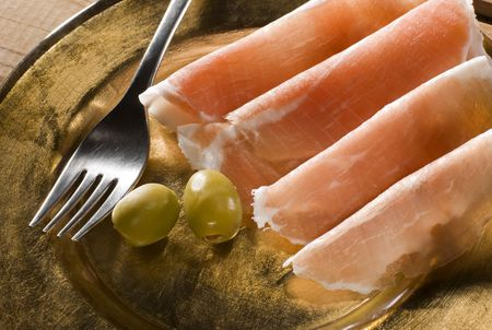 fresh prosciutto with olive fruits close up shoot photo