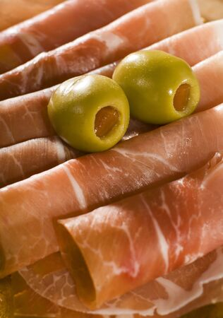 prosciutto: fresh prosciutto with olive fruits close up shoot Stock Photo