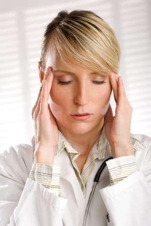 dolor de cabeza: bella mujer joven m�dico en el estr�s retrato  Foto de archivo