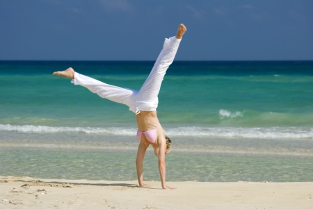 young blond woman making cartwheel on the beach photo