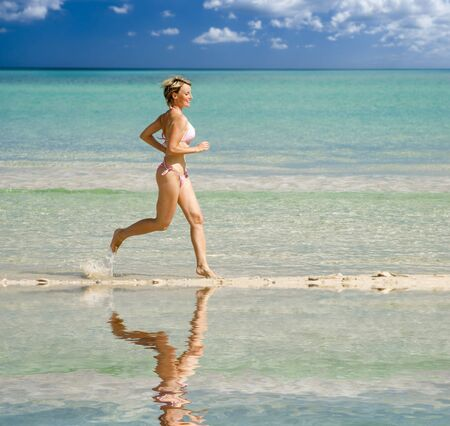 young blond woman running on the beach photo