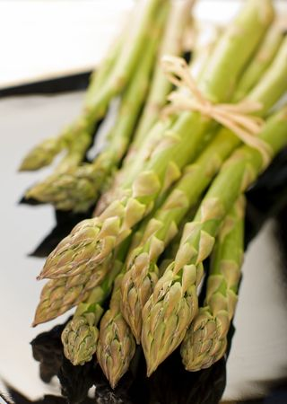 green fresh asparagus on black plate close up Stock Photo - 3039620