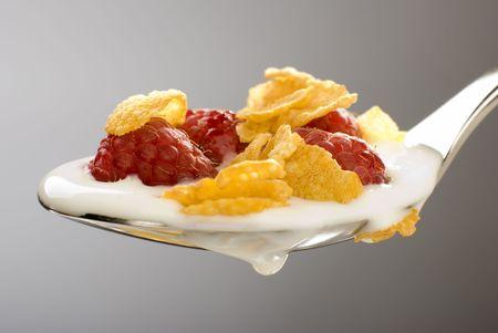 corn flakes, fresh raspberry and yogurt on the spoon close up