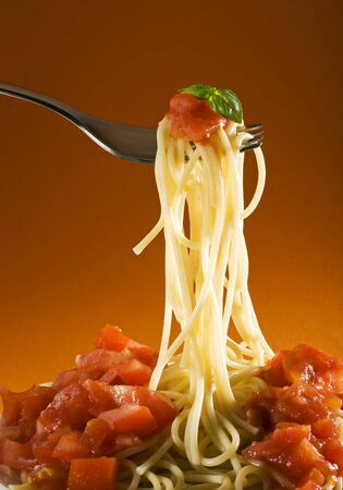 spaghetti with tomato and basil on fork close up Stock Photo