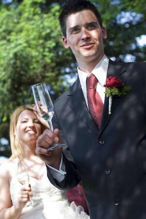 young groom toasting with bride in background photo