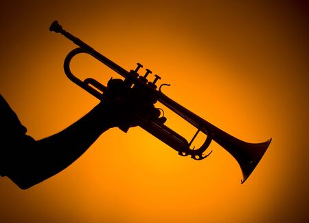 backlights: backlight hand holding trumpet on orange background