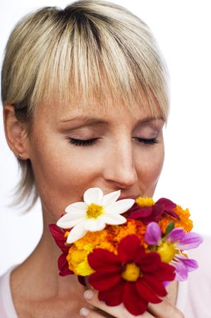 young blond woman smelling flowers close up photo
