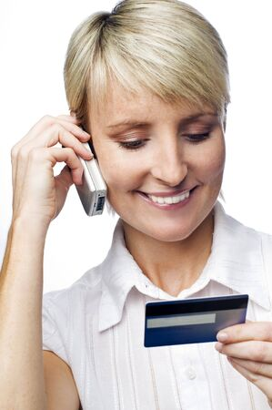 young woman talking on the phone looking on credit card photo