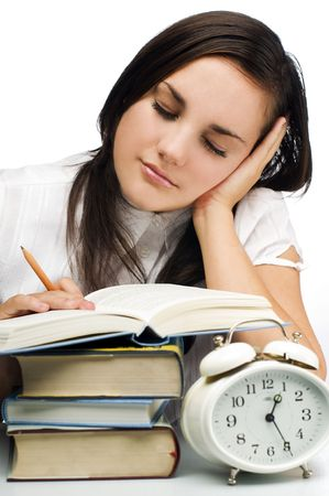 tired young woman sleeping on a stack of books photo
