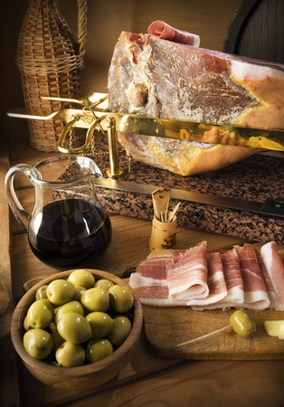 prosciutto: sliced prosciutto with red wine and olives close up shoot