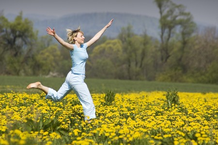 young blond happy woman running on grass photo
