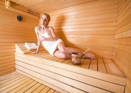 body temperature: young blond woman sitting in sauna - health