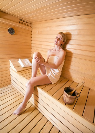 young blond woman relaxing in sauna close up photo
