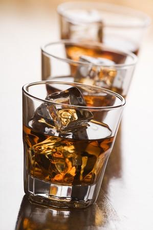 distilled: bicchiere di whisky con ghiaccio vicino sparare