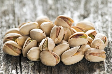 beautiful pistachio seeds on wood close up photo