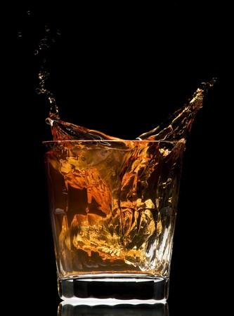 distilled: whiskey schizzi su sfondo nero vicino Archivio Fotografico