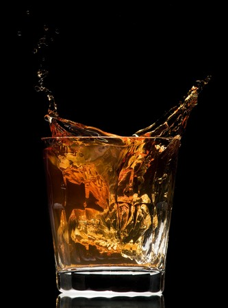 hard liquor: whiskey splash on black background close up