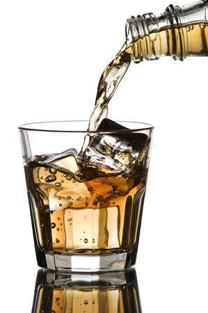 intoxicant: Whiskey essere versato in un vetro su sfondo bianco Archivio Fotografico